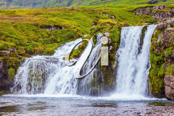 Cloudy day in Iceland. Cascade falls on the green grass mountain