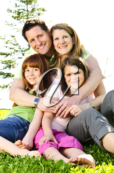 Portrait of happy family of four sitting on grass at the park hugging