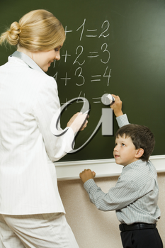 Photo of elementary student doing sums on blackboard and looking at his teacher who is helping him