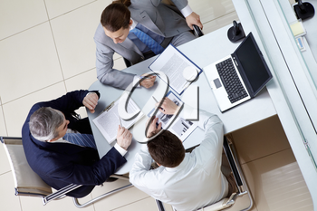 View from above of business men sitting at table in the office and discussing new plan
