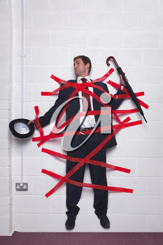Businessman holding an umbrella and bowler hat stuck to a wall with red tape.