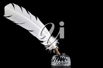 A white feather quill pen and crystal glass ink well isolated on a black background.