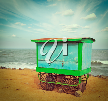 Vintage retro hipster style travel image of cart on beach. Tamil Nadu, India