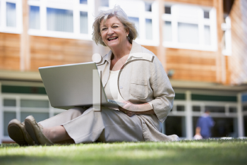 Royalty Free Photo of an Older Woman Sitting on the Lawn With a Laptop