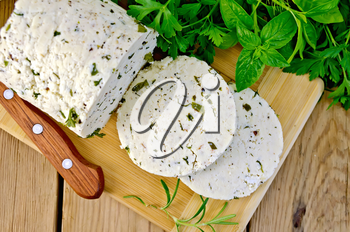 Homemade cheese with herbs and spices, cut into slices, knife, parsley, rosemary, basil, napkin on wooden board on top