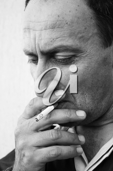 Royalty Free Photo of a Man Smoking a Cigarette