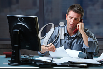 Mid-adult businessman speaking on landline phone working overtime in office checking papers.
